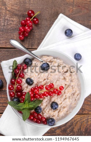 Oatmeal with berries in a bowl on a brown wooden table. breakfast. healthy food. top view #1194967645