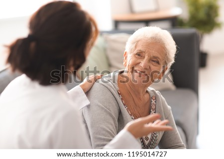 Young doctor visiting elderly woman at home Royalty-Free Stock Photo #1195014727