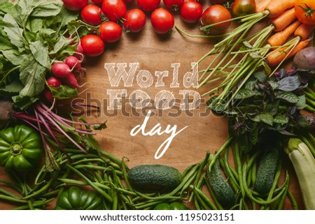 "Frame of healthy green and red vegetables on wooden table with ""world food day"" lettering #1195023151"