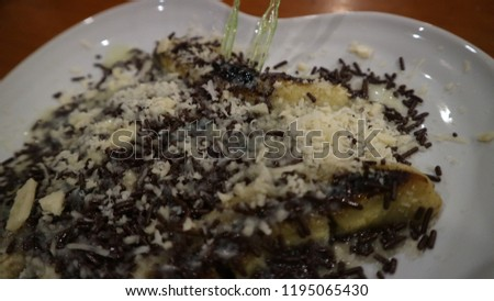 Bananas with chocolate and cheese on the white plate #1195065430