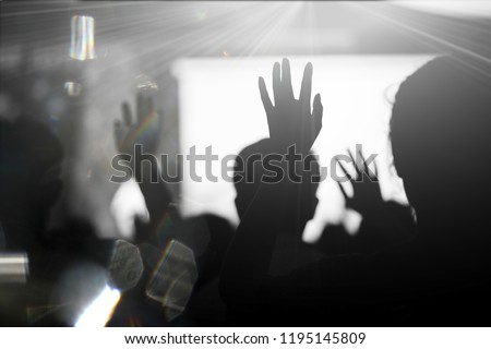 Blurred photo of Christian worship God together in Church hall in front of music stage.raised hand and praise the LORD.Music concert background. #1195145809