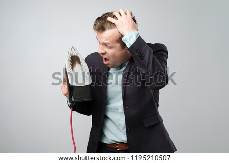 European mature man in suit holding electric iron with dirty burned spot on white background