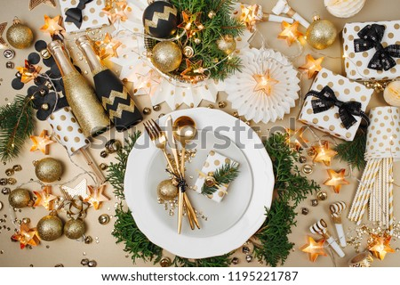 Christmas table setting. Gold and black decoration with with gift and fir-tree branch. Flat lay, top view.  #1195221787