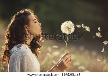 Beautiful Young Woman sitting on the field in green grass and blowing dandelion. Outdoors. Enjoy Nature. Healthy Smiling Girl on summer lawn. Allergy free concept. Gorgeous slim mixed race Caucasian #1195258168