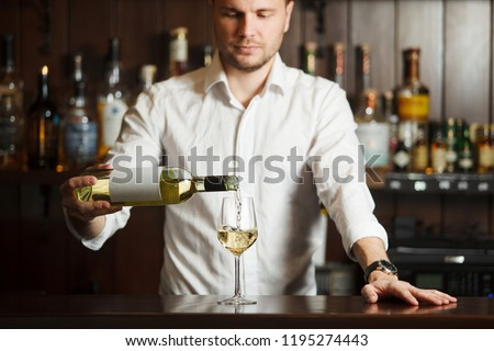Sommelier in shirt pouring white wine into glass placed on broad bar counter, man wine steward filling wineware with dine beverage alcoholic drink, rows of bottles on blurred background #1195274443