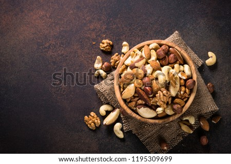Assortment of nuts in wooden bowl on dark stone table. Cashew, hazelnuts, walnuts, almonds, brazilian nuts and pine nuts. Top view with copy space. Royalty-Free Stock Photo #1195309699