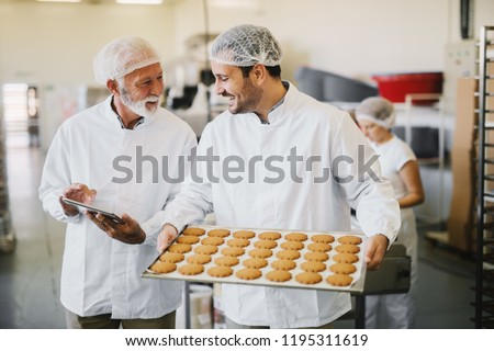 Picture of two employees in sterile clothes in food factory smiling and talking. Younger man is holding tray full of fresh cookies while the older is holding tablet and checking production line. #1195311619