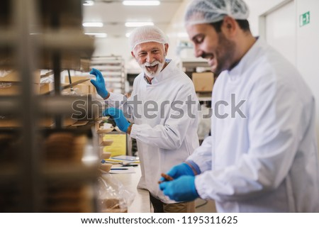 Picture of two male food factory employees in sterile clothes packing fresh made cookies and having fun. #1195311625