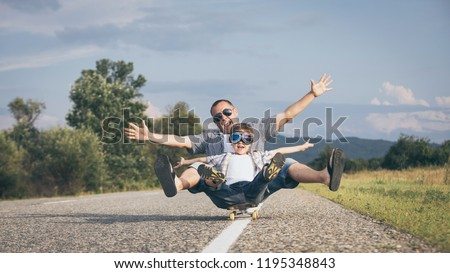 Father and son playing on the road at the day time. People having fun outdoors. Concept of friendly family. #1195348843