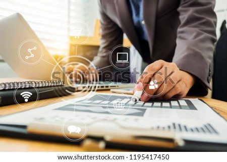 business documents on office desk with laptop and graph business diagram and man working at office. #1195417450