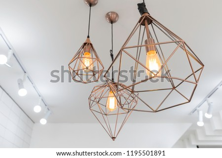 retro copper hanging lamp with orange light bulb. #1195501891
