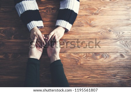 man and a woman holding hands at a wooden table #1195561807