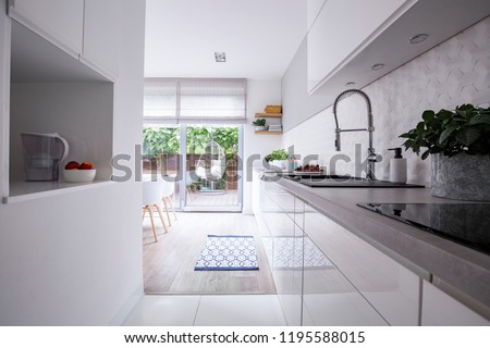 View of kitchen interior with cupboards and glass door for terrace. Real photo