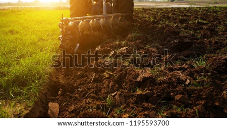 Agricultural workers with tractors.The tractor harvester working on the field. Tractor plowing field with Soft light from Sunlight. #1195593700