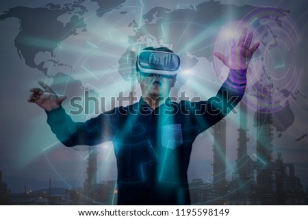 Portrait of businessman in virtual reality glasses working in oil industry discussing a new project with large oil refinery background.Double exposure. Elements of this image furnished by NASA #1195598149