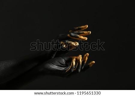 Hands of woman with black and golden paint on her skin against dark background #1195651330