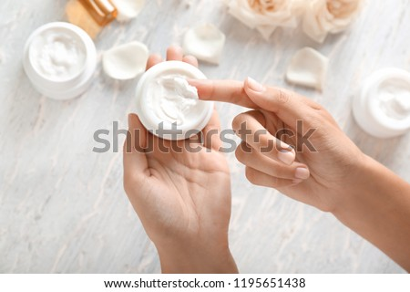 Young woman applying body cream, closeup Royalty-Free Stock Photo #1195651438