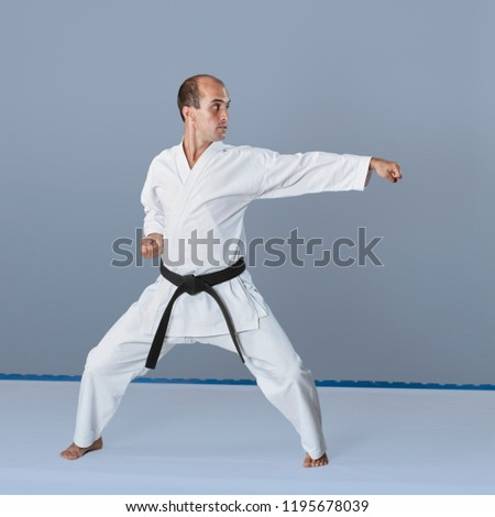 Active young athlete trains formal karate exercises #1195678039