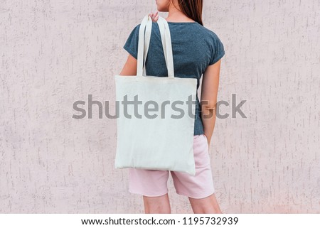 Young woman with white cotton bag in her hands. #1195732939