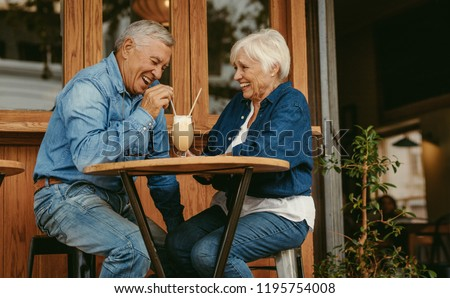Cheerful old couple sitting at cafe having a coffee. Senior man and woman sitting at restaurant table talking with cold coffee on table. #1195754008
