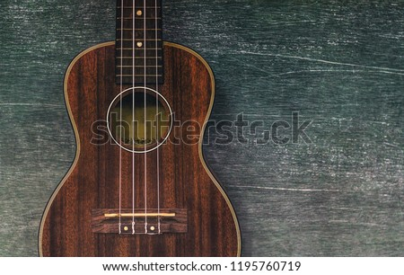 Brown ukulele guitar portrait on texture Wall plaster ,Vintage dark tone holiday relax break time with music or art concept with copy space for your text  #1195760719