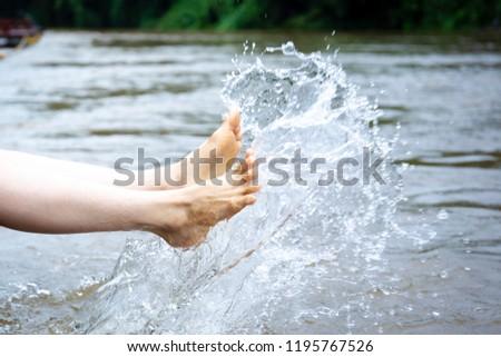 Girl enjoying with splashing water beside the river close up. #1195767526