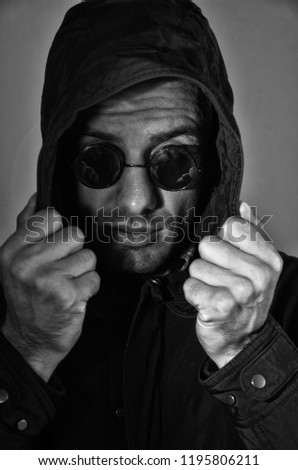 black and white portrait of a young man in a hood and in round sunglasses on a gray background #1195806211