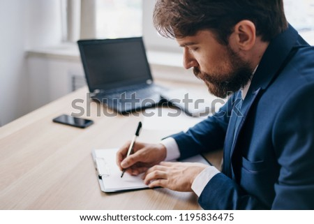man writing in notebook at his desk                             #1195836475