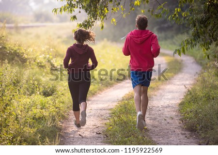 young couple enjoying in a healthy lifestyle while jogging along a country road, exercise and fitness concept #1195922569
