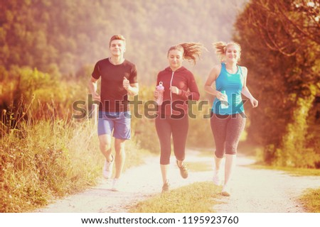 group of young people jogging on country road runners running on open road on a summer day #1195923760