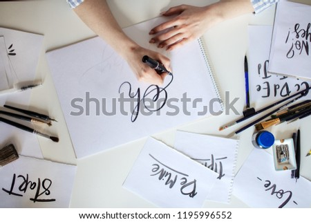Top view of hand of girl with pen writes on paper with ink #1195996552