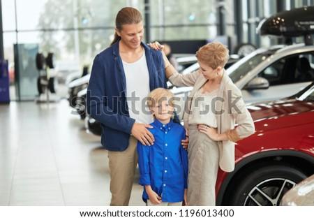 Happy family near new car. Auto dealership centre #1196013400