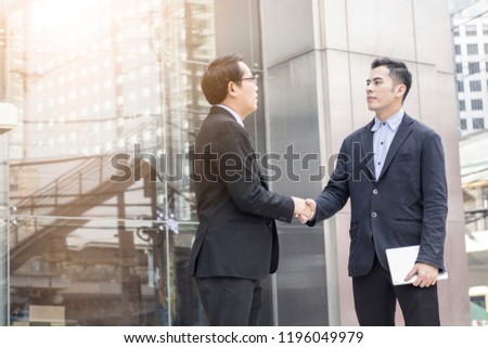 Successful negotiating business concept, Businessmen shaking hands after finishing meeting or setting  goals and planning way to success in front of building   #1196049979