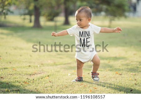 Baby toddler on the lawn. Enthusiastic and excited In the morning of the day, the air is clear, sunny and light. #1196108557