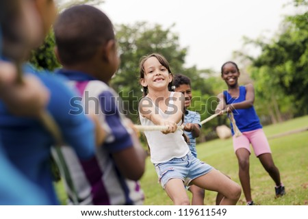 Children and recreation, group of happy multiethnic school kids playing tug-of-war with rope in city park. Summer camp fun #119611549