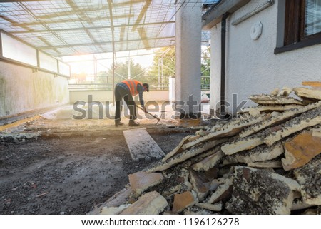 Home repair. Rebuilding waterproofing and insulation of a terrace – roof, removal and stacking of the old insulating (polyurethane). Backlit worker with pickaxe Royalty-Free Stock Photo #1196126278