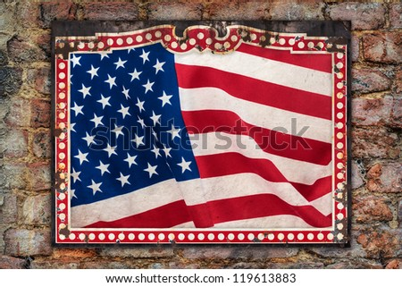 Weathered US flag inside a vintage metal frame on an ancient brick wall
