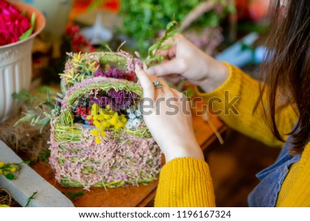 Female hands making beautiful bouquet and composition of flowers on background #1196167324