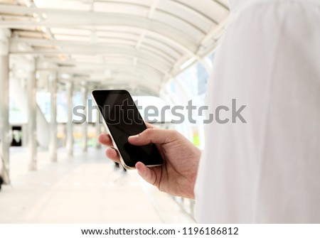 Business man holding mobile about to call customer. manager using mobile phone. blank phone screen. Blurred background. Business financial saleman concept. #1196186812