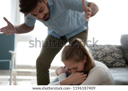 Unhappy crying frightened woman and aggressive man quarrelling at home. Angry husband emotionally arguing screaming shouting to scared wife psychological emotional abuse and domestic violence concept #1196187409