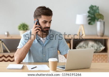Serious businessman sitting at the desk typing chatting using computer and talking by cellphone. Confident employee hard working busy during work day solving business matters agent talking with client #1196195266