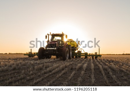 Planting Sorghum during sunset on a farm in the Australian outback.  #1196205118
