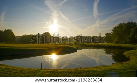 Golfcourse sunrise reflexion in the water