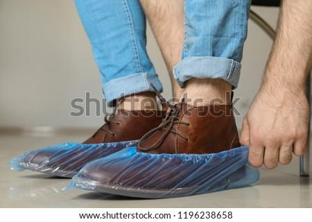 Man putting on blue shoe covers, closeup #1196238658