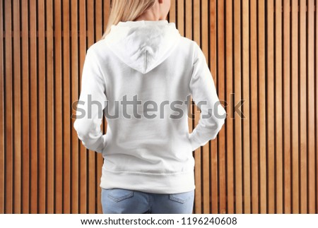 Woman in hoodie sweater on wooden background. Space for design #1196240608