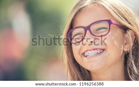 Portrait of a happy smiling teenage girl with dental braces and glasses. #1196256388