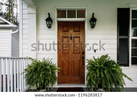 Brown Wood Front Door of a White Siding Southern House Royalty-Free Stock Photo #1196283817