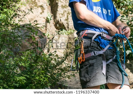 PERVOMAISK, UKRAINE  – 27 September, 2018: Close-up of thigh climber with equipment on belt, stands near rock. Easy belay-descender device in the hands of climber closeup. Climbing gear and equipment #1196337400