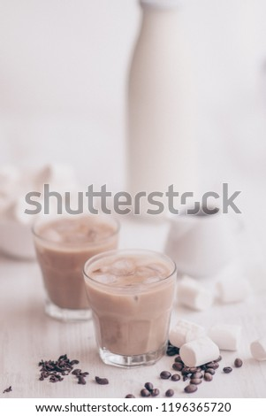 Light background. Iced coffee. Concept of a cooling drink. Marshmelow and coffee beans on the table. Summer drink. Cold coffee with milk and chocolate. #1196365720