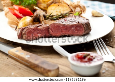 Overhead view of delicious,grilled beef steak with roasted potatoes and fresh green herb salad on an old wooden table #1196391196